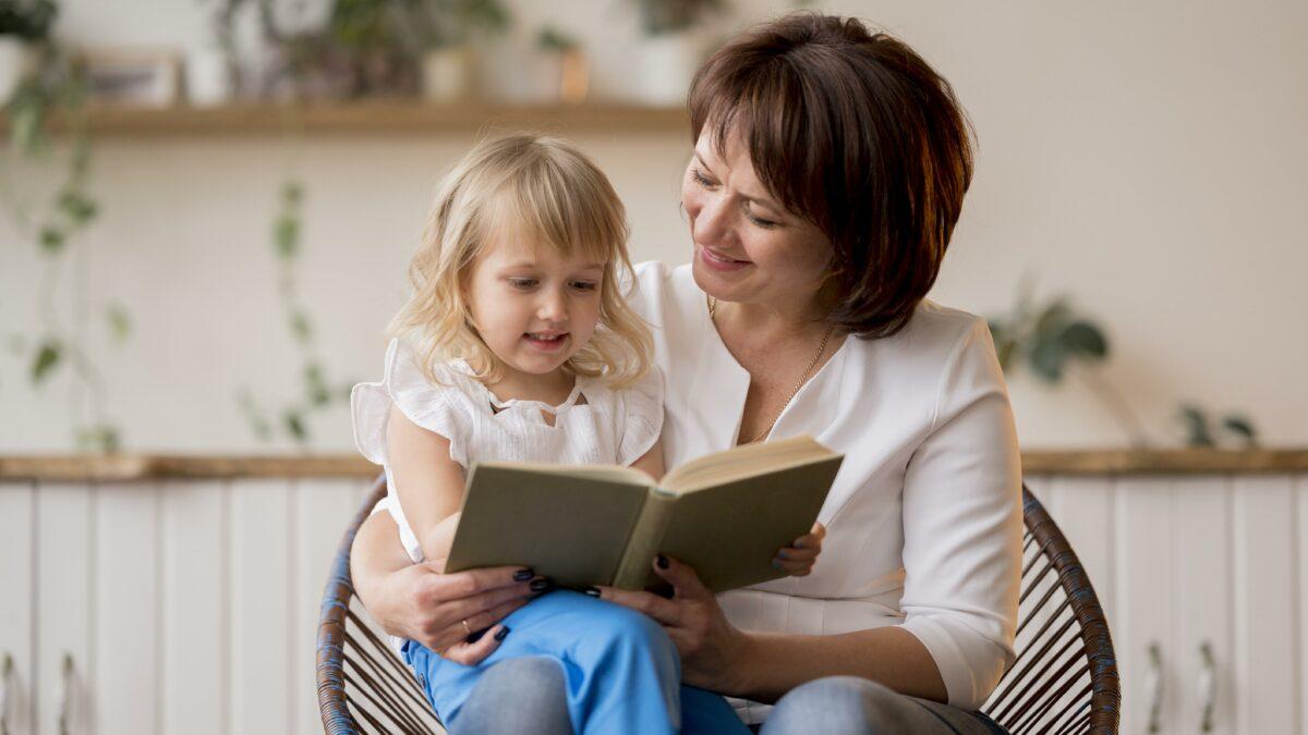 Avo ensinando a neta com um livro Desperta Debora 1