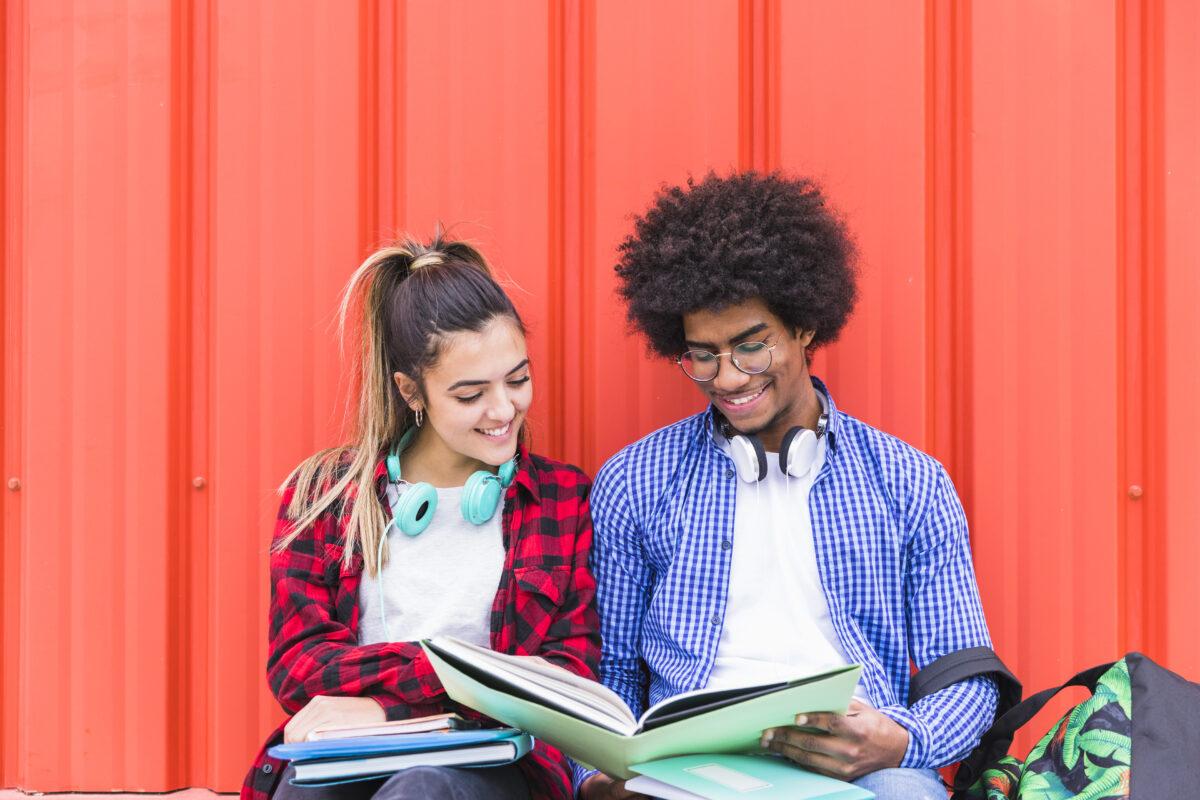 Casal de Estudantes lendo um livro em fundo laranja Desperta Debora