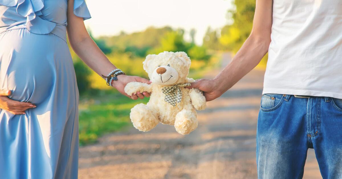 Casal gravido segurando um ursinho ao ar livre Desperta Debora