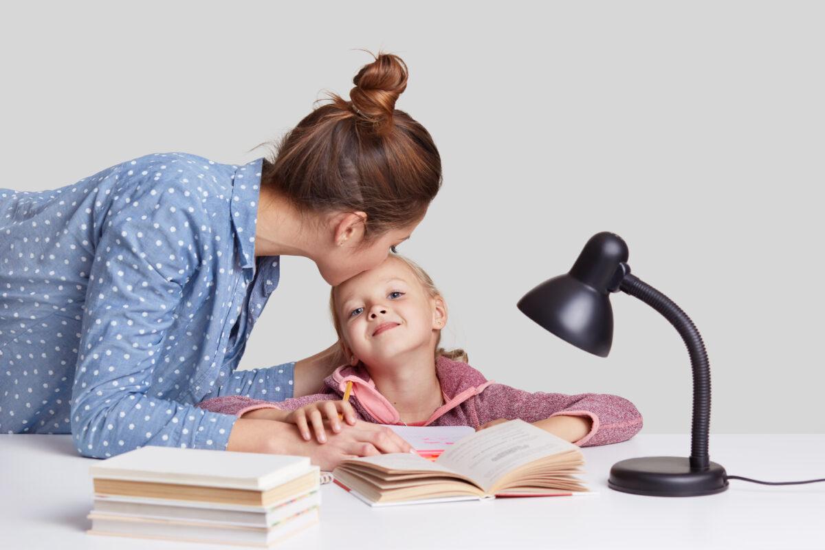 Mae jovem beijo na testa da filha ensinando a materia sob a luz Desperta Debora