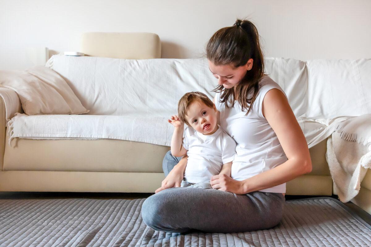 Mae sentada ao chao com seu filhinho portador de sindrome de down Desperta Debora