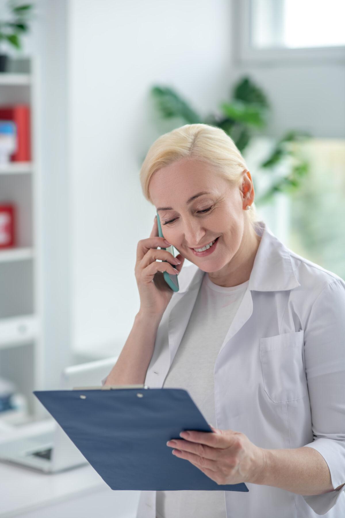 Mulher idosa no telefone prevalece o branco com prancheta Desperta Debora