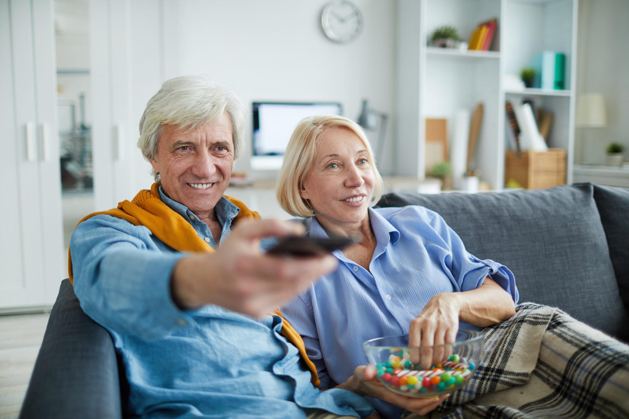 casal feliz de blusa azul assistindo TV com petisco Desperta Débora