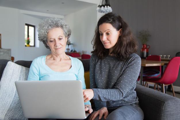 mulher jovem explicando vovo como uso laptop sobre o Desperta Débora