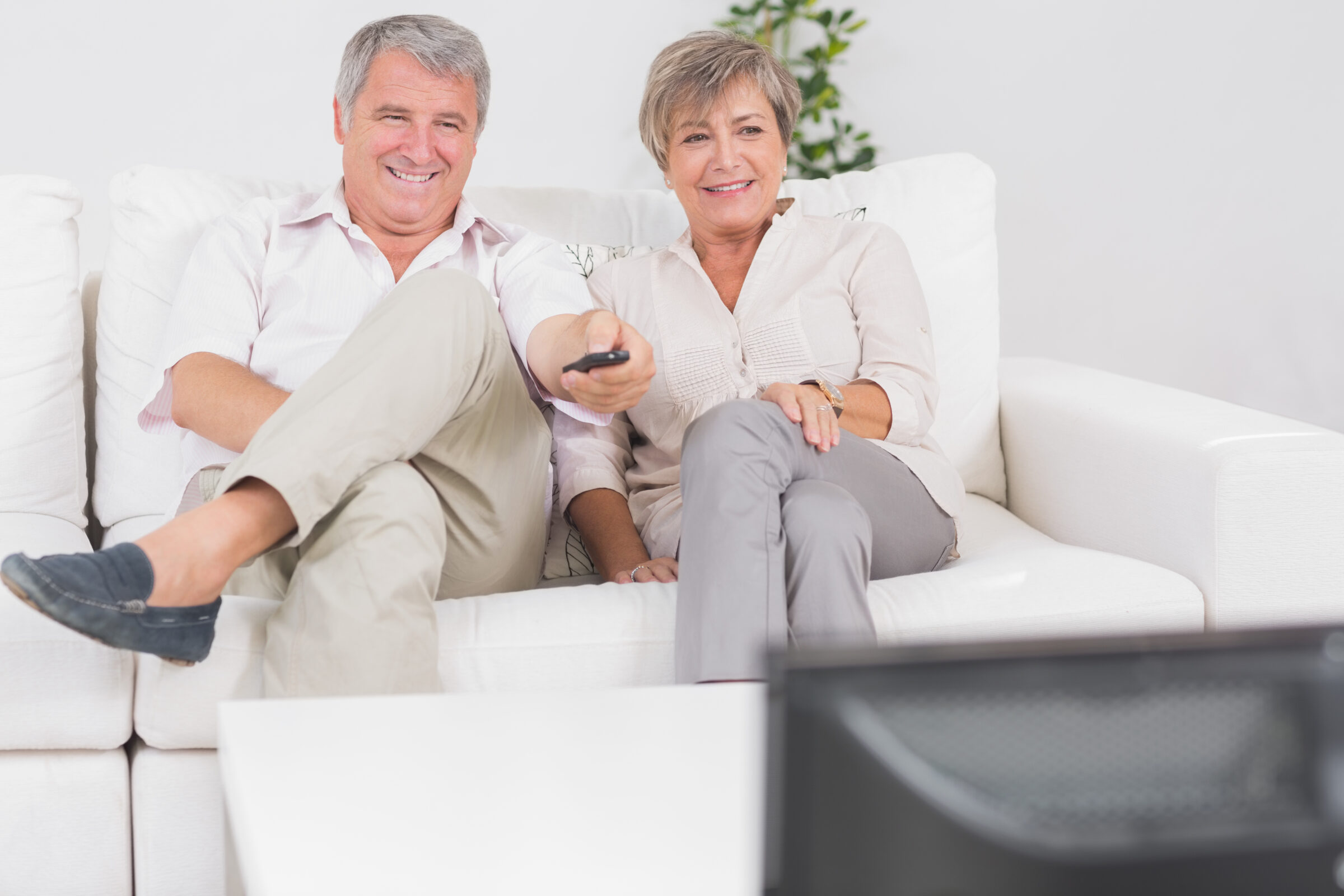 Casal de idosos assistindo TV em sofa brancoe controle na mão Desperta Débora